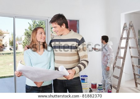 Young couple looking at each other with painter in background