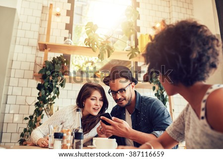 Young couple looking at smart phone while sitting in cafe with friends. Group of young people sitting at a table in restaurant and using mobile phone.