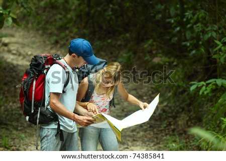 Young couple looking at the map in the forest