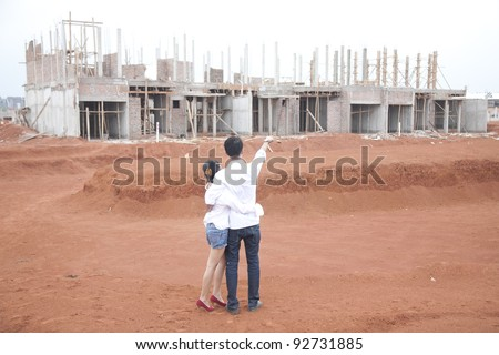 Young couple looking at their new investment, still under construction