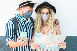 Young couple looking city map app during vacation tour while wearing face protective masks for coronavirus spread prevention - Travel, Covid 19 lifestyle and healthcare concept - Focus on girl face