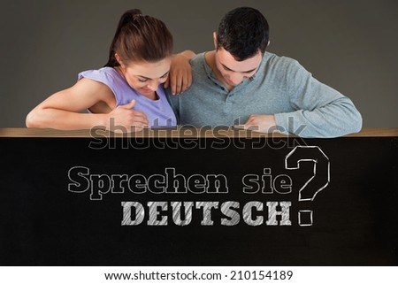 Young couple looking down a wall against blackboard on wall, Do you speak German?