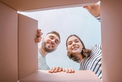 Young couple looking inside cardboard box, bottom view