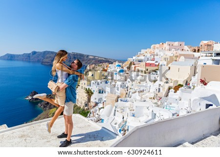 Young couple looks down on the landscape of the island of Santorini Stockfoto ©
