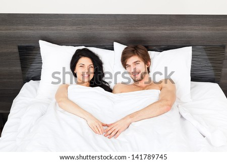 young couple lying in a bed, happy smile man and woman lovers in bedroom, hold hands heart shape valentine day concept