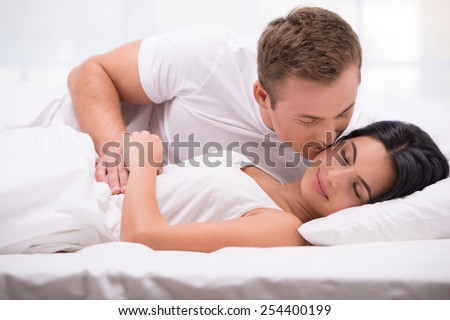 Young couple lying in white bed early in the morning. Handsome man kissing his sleeping wife