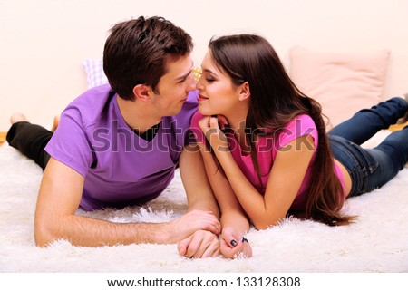Young couple lying on carpet at home