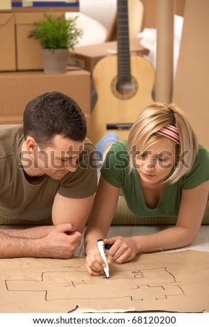 Young couple lying on floor of new house planning home together on paper.