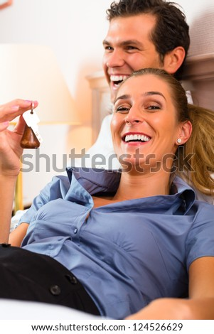 Young couple lying on the bed in the hotel room and the woman has a key in his hand