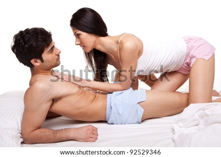 Young Couple lying on top of a bed and staring intently into each others eyes with love.