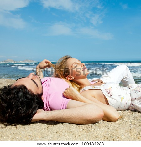 Young couple lying together on a sand by sea and looking to a sky