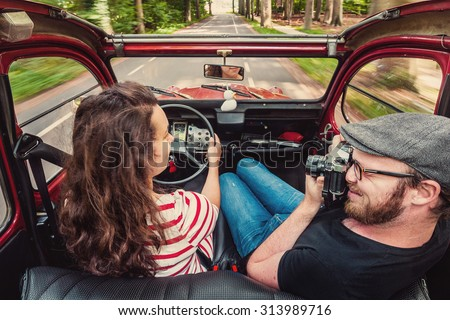 Young couple making a road trip in an old simple comvertibel classic car, looking at eachother and taking pictures.