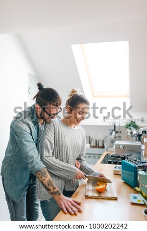 Young couple making breakfast and having fun