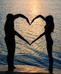 young couple making heart shape with arms on beach against golden sunset