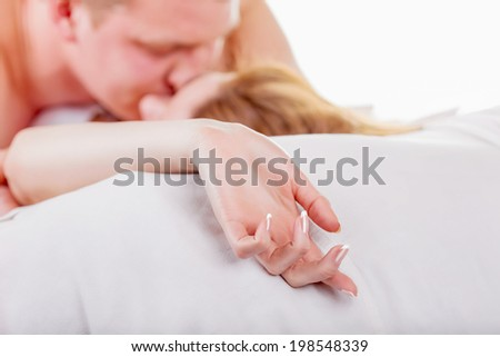 Young couple making love in bed. Focus on hand