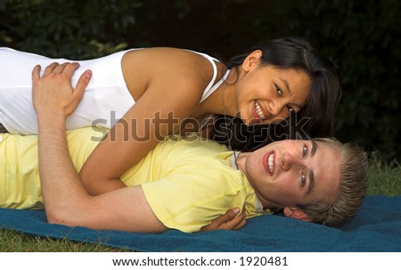 Young couple making love on a beach towel