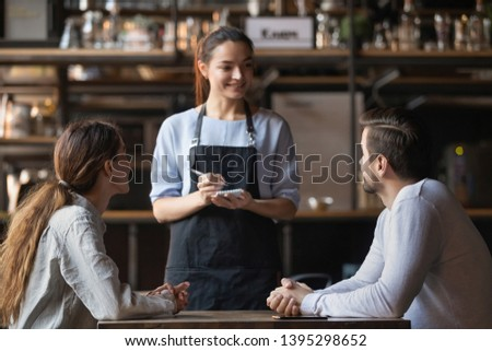 Young couple making order in cafe, attractive smiling waitress serving customers, writing in notepad, coffeehouse female worker talking with man and woman about menu, offering food and drinks