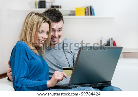 Young couple making shopping online with credit card at home