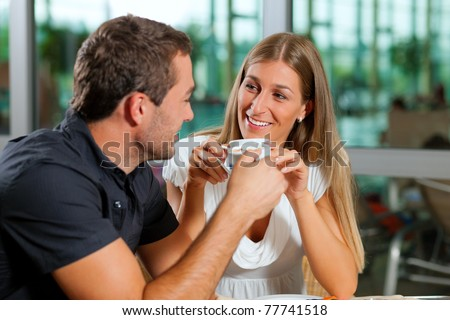 Young couple - man and woman - drinking coffee in a cafe in front of a glass facade