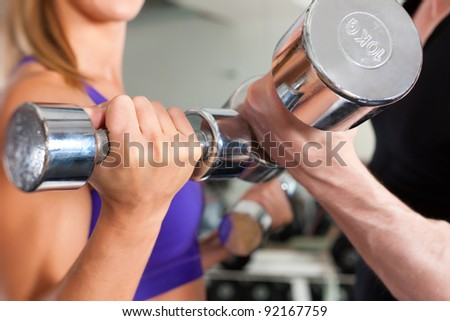 Young couple - man and woman - is exercising with barbell in gym to strengthen the muscles