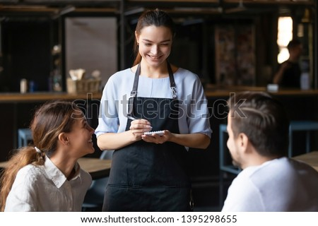 Young couple, man and woman ordering food in cafe, smiling waitress serving customers, attractive coffeehouse female worker talking with clients, consulting guests about menu, writing in notebook
