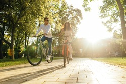Young couple man and woman ride a bike in the park in the autumn season on a background of sunset. Cycling on the weekend with a friend.