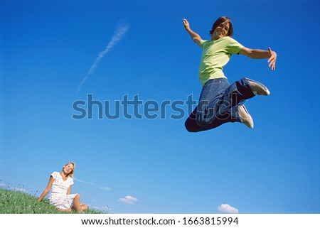 Young couple, man jumping in mid-air