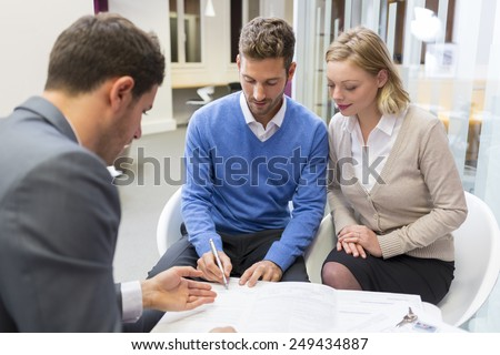 Young couple meeting real-estate agent for house investment. Signing a contract Foto stock ©