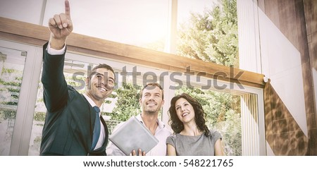 Young couple meeting real-estate showing a house project on a digital tablet