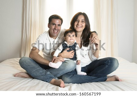 Young couple mother father and baby girl sitting on bed isolated portrait