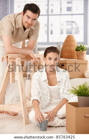 Young couple moving home, sitting on floor, boxes around, smiling, drinking tea.?