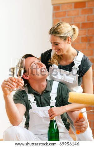 Young couple moving in new flat doing renovation and painting, celebrating their new home with sparkling wine