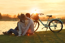 Young couple near lake at sunset. Perfect place for picnic