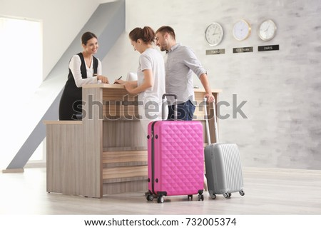 Young couple near reception desk in hotel