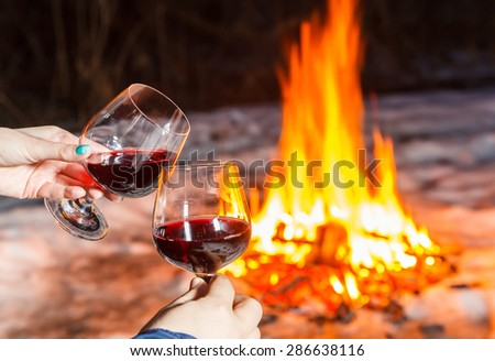 Young couple near the bonfire with two glasses of red wine