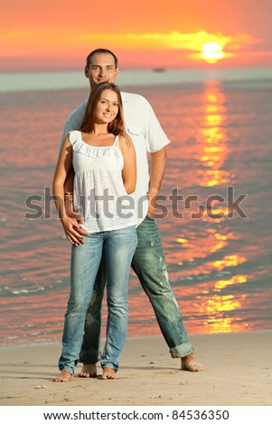 Young couple near the sea at sunrise