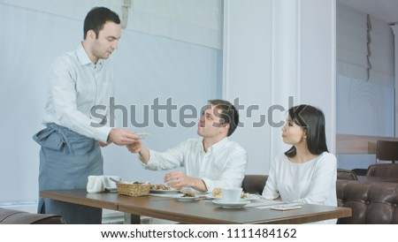 Young couple not liking their food and asking waiter to take it away