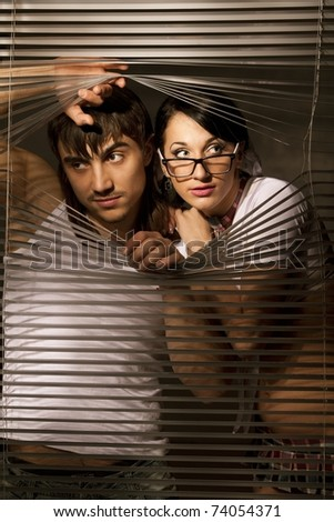 Young Couple observing through a jalousie