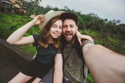Young couple of backpackers take selfie self-portrait near rice fields in Bali while travel on honeymoon. Happy couple in love take funny selfie for travel blog.