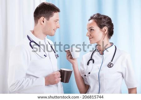 Young couple of doctors having coffee break