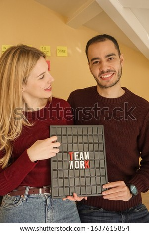 Young couple of entrepreneurs hold a picture representing Team Work. They collaborate in a startup, and each squad is cross-functional to facilitate growth.