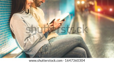 Young couple of friends using mobile phones inside subway train station - Millennials people having fun with technology trends in urban context - Tech and city lifestyle concept - Focus on girl hand