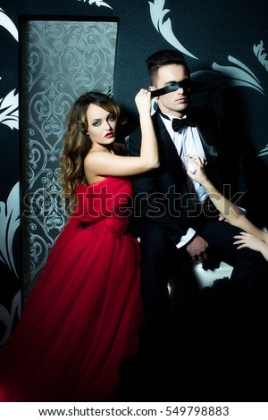 148f6539722d8 young couple of handsome man in black suit and bow with pretty sexy woman  in red