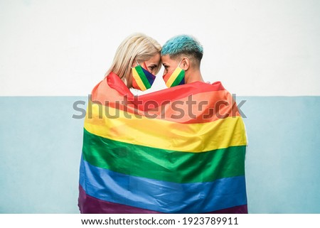 Young couple of lesbian women under lgbt rainbow flag wearing masks at gay pride parade - Focus on faces
