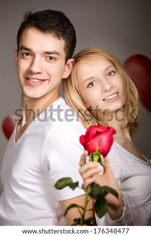 Young couple of lovers. Man presents flower