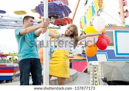 Young couple of teenagers visiting a fun fair ground with rides and lights around them, holding balloons, being playful and joyful during a sunny day.