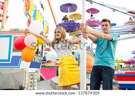 Young couple of teenagers visiting a fun fair ground with rides and lights around them, holding balloons and being playful during a sunny day.