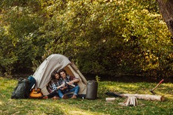 Young couple of tourists are exploring new places together. Attractive young woman and handsome man are spending time together on nature. Sitting in touristic tent in forest and drinking tea.