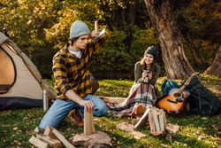 Young couple of tourists are exploring new places together. Handsome man chopping wood with axe. Attractive woman drinks tea and sitting on the log. Trevel concept. Boyfriend is tired from job.