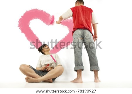 Young couple of workers painting heart on a wall with roller - stock photo